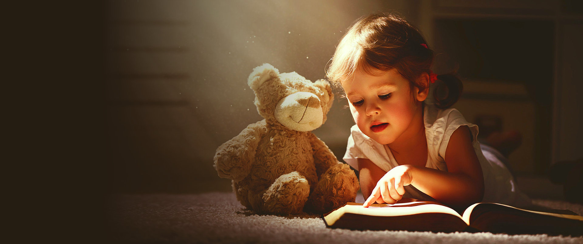 little girl with her teddy bear reading a book